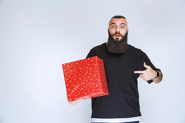 Man met baard met een rode geschenkdoos en kijkt verward en doodsbang.