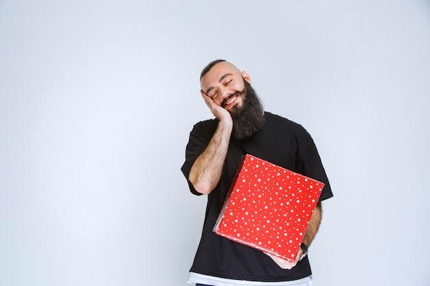 Man met baard met een rode geschenkdoos en ziet er moe uit.