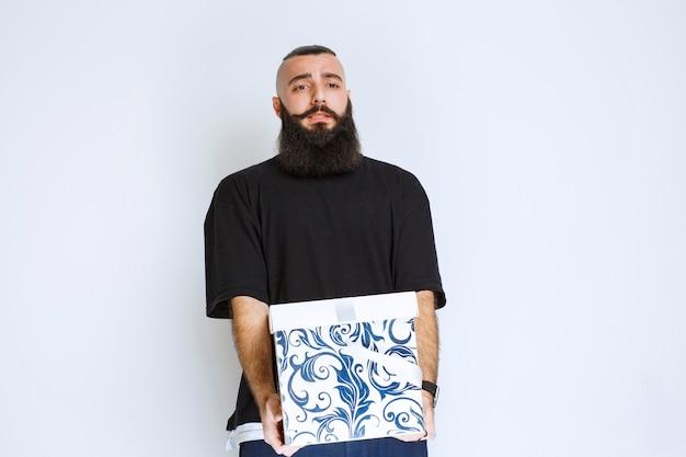 Man met baard met een witblauwe geschenkdoos en ziet er teleurgesteld uit.