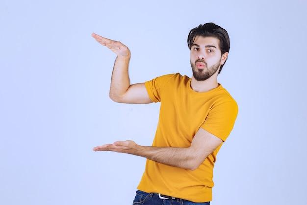 Man met baard met geschatte afmetingen van een object.