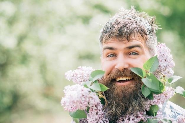 Man met baard van bloemen. gelukkig bebaarde man glimlach met lila bloemen op zonnige dag