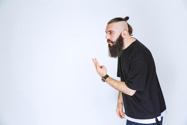 Man met baard wijzend naar iemand in de buurt.