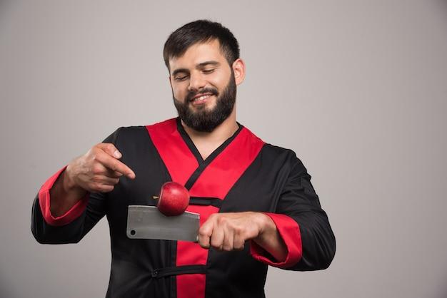 Man met baard wijzend op rode appel op mes.