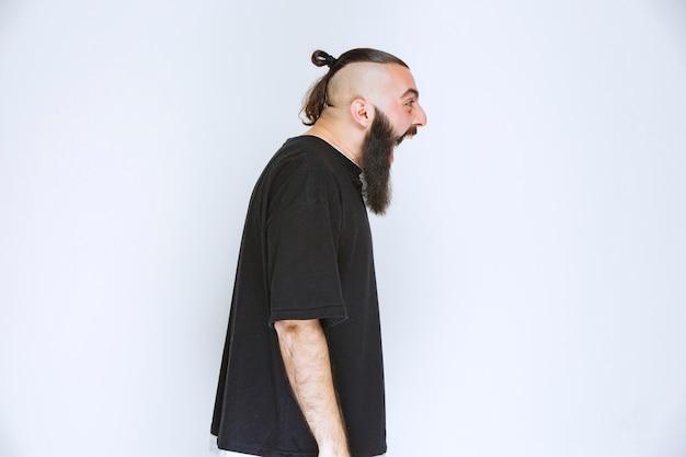 Man met baard ziet er agressief en teleurgesteld uit.