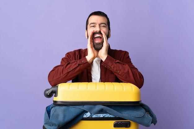 Man met bagage over geïsoleerde paarse achtergrond