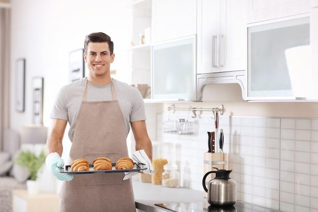 Man met bakplaat met heerlijke zelfgemaakte croissants in keuken