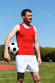 Man met bal en blauwe lucht in de zomer
