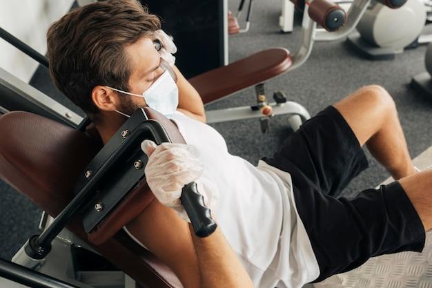 Man met behulp van apparatuur in de sportschool terwijl hij medische masker draagt