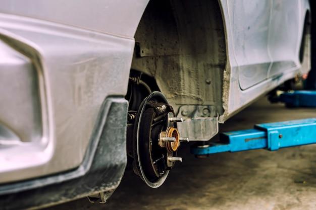 Man met behulp van automonteur blokkeer het windwiel. om uw banden en remmen voor auto te controleren. auto monteur voorbereiding voor het werk.