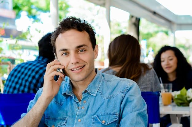Man met behulp van de mobiele telefoon en koffie drinken