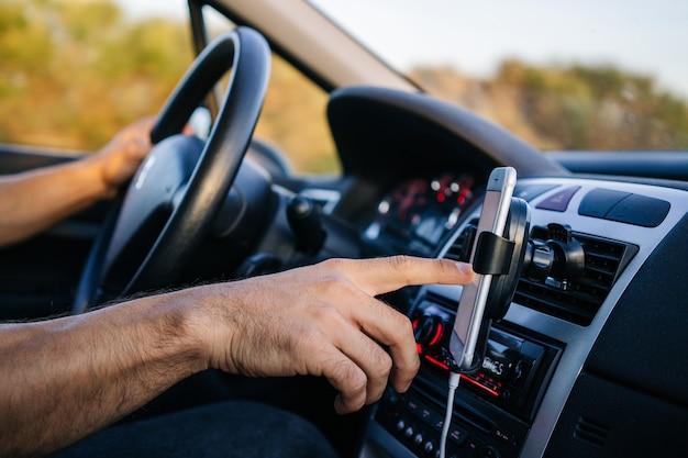 Man met behulp van de telefoon tijdens het rijden