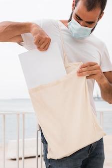 Man met behulp van een recyclebare boodschappentas en masker dragen