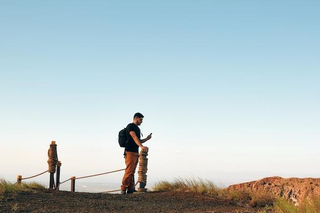 Man met behulp van een slimme telefoon na een wandelpad in de bergen