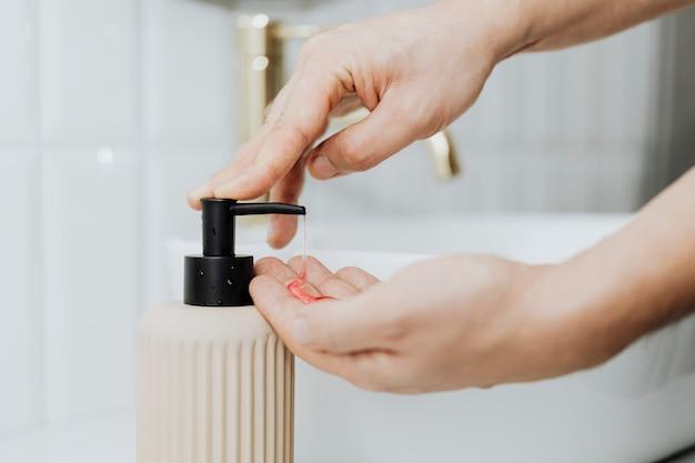 Man met behulp van een zeepdispenser