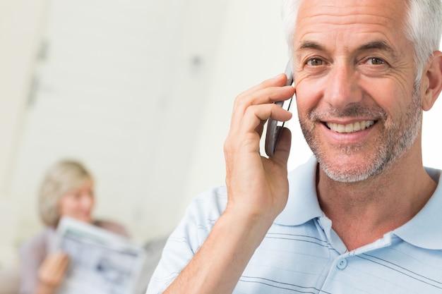 Man met behulp van mobiele telefoon met vrouw krant thuis lezen