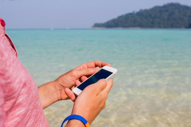 Man met behulp van mobiele telefoon op het strand