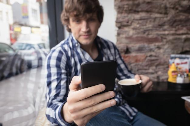 Man met behulp van mobiele telefoon terwijl het drinken van koffie