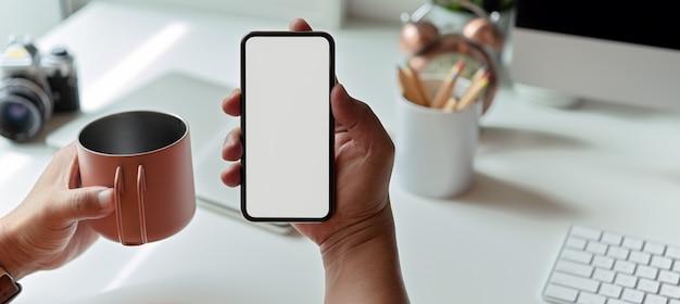 Man met behulp van mock-up smartphone en koffiemok zittend op de werkruimte