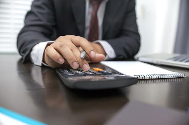 Man met behulp van rekenmachine en schrijven opmerking maken met berekenen.