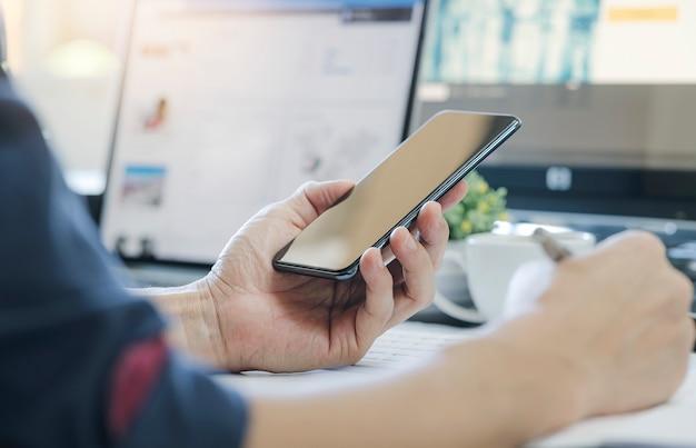 Man met behulp van smartphone tijdens het werken op modern kantoor, leeg scherm voor grafische weergave.