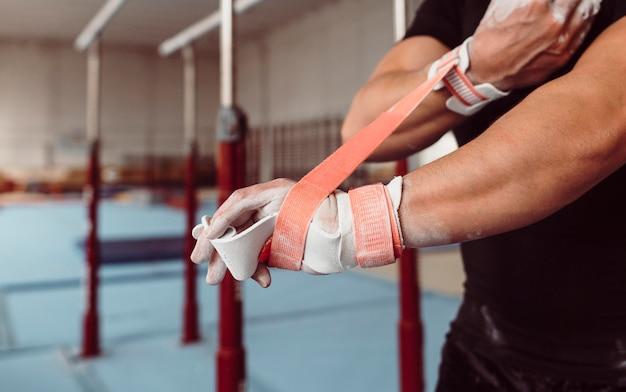 Man met behulp van speciale apparatuur voor gymnastiekopleiding