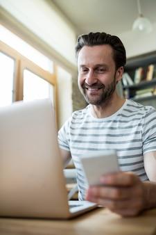 Man met behulp van zijn laptop en mobiele telefoon in de koffiebar