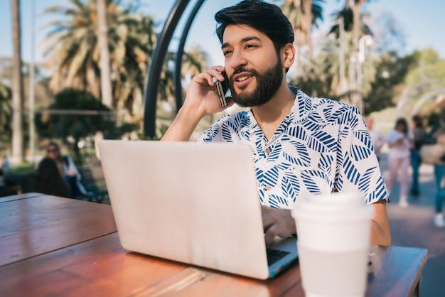 Man met behulp van zijn laptop en praten over de telefoon.