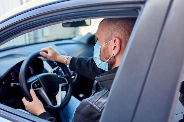 Man met beschermend masker besturen van een auto door de pandemie van de coronavirus quarantaine
