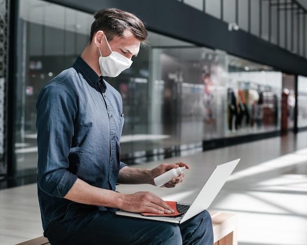 Man met beschermend masker desinfecteert zijn laptop