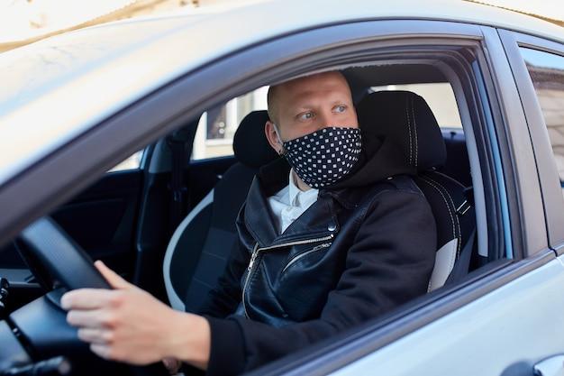 Man met beschermend masker die een auto adresseren door pandemie van het coronavirus in quarantaine te plaatsen