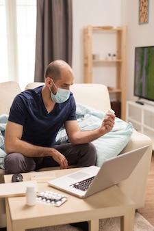 Man met beschermingsmasker die pillenfles bekijkt tijdens zelfisolatie.