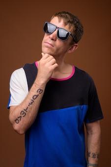 Man met blauw shirt en zonnebril tegen bruine muur