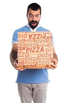 Man met blauw shirt met een pizza doos