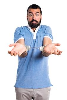 Man met blauw shirt met handboeien