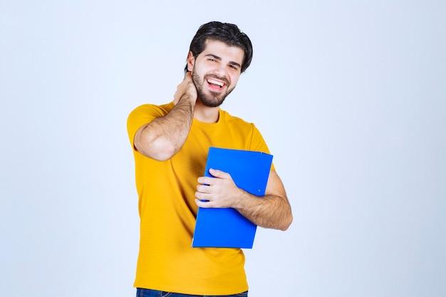 Man met blauwe map die vriendelijke en rustige poses geeft.