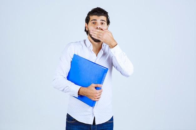 Man met blauwe map kijkt verward of doodsbang