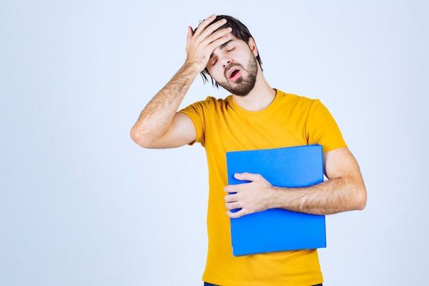 Man met blauwe map kijkt verward