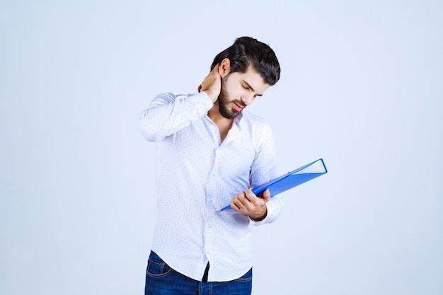 Man met blauwe map ziet er uitgeput en ontevreden uit
