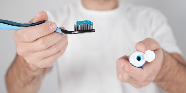 Man met blauwe tandpasta en tandenborstel.