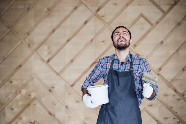 Man met blikje verf en penseel opzoeken op een houten muur