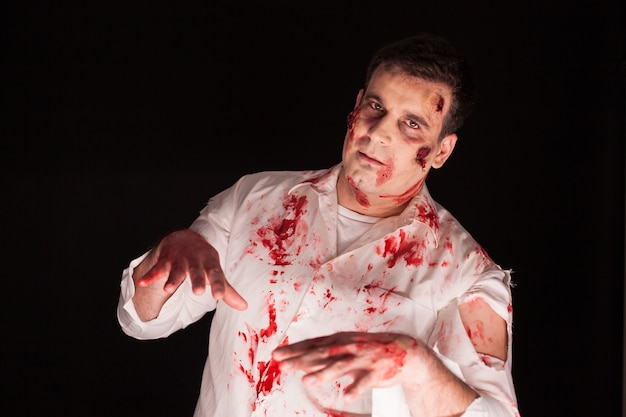 Man met bloedige littekens bezeten door demon op zwarte achtergrond voor halloween. creatieve make-up.