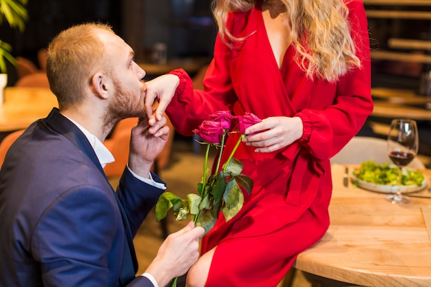 Man met bloemen kussen hand van de vrouw
