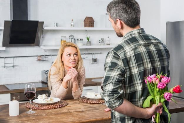 Man met bloemen van terug en vrouw in de keuken