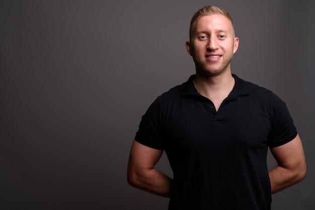 Man met blond haar dragen zwarte poloshirt op grijze muur