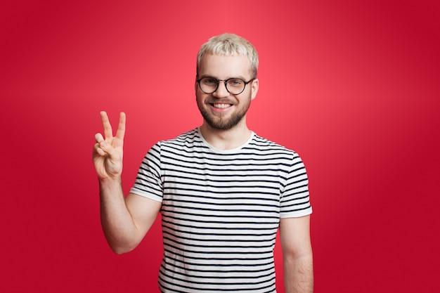 Man met blond haar en baard gebaart het vredesteken op een rode muur glimlachend in de camera