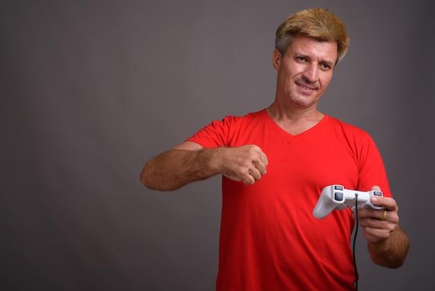 Man met blond haar, gekleed in een rood shirt tegen een grijze muur