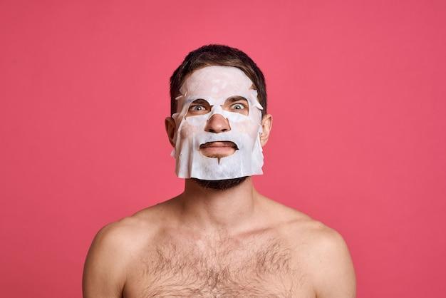 Man met blote schouders in een wit masker helder roze huid