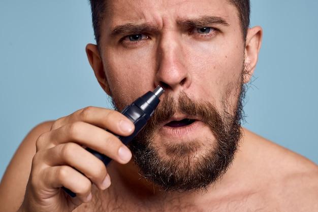 Man met blote schouders verwijdert neus haar hygiëne zorg blauwe ruimte