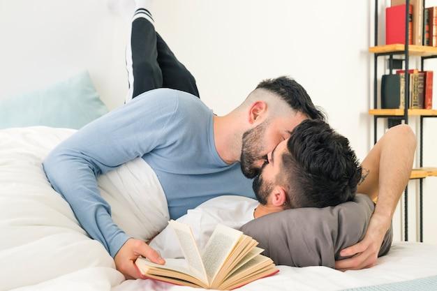 Man met boek in de hand kussen zijn vriend liggend op bed