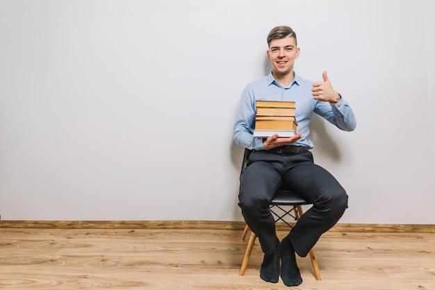 Man met boeken duim-omhoog gebaren